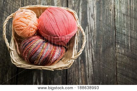 Three balls of yarn in square woven basket. Background of wood plank. Copyspace