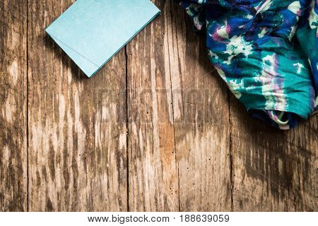 Journal and scarf against wood plank background. Copyspace.
