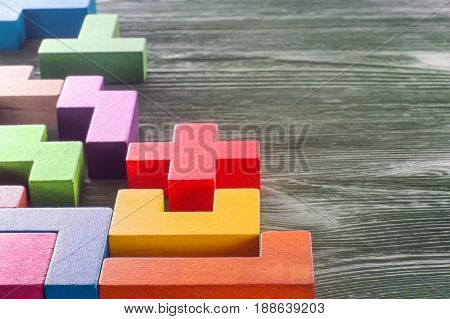The concept of creative logical thinking. Geometric shapes on a wooden background. Abstract construction from wooden blocks with copy space.