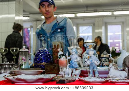 Moscow, Russia - March 19, 2017: Old antique porcelain and ceramic figures for sale on the flea market. Toy and collectibles. Selective focus, antiques dealer in the background