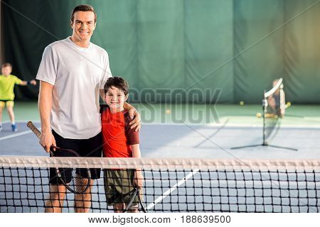 Tennis is our favorite game. Cheerful father and son are standing on tennis court and embracing. They are looking at camera with happiness and smiling. Portrait and copy space in right side