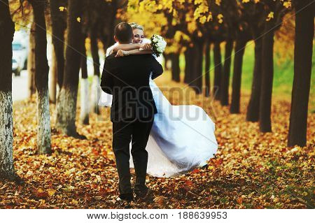 Happy Bride Holds Groom's Neck Tightly While He Whirls Her On The Fallen Leaves