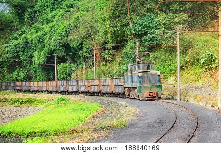 Electric narrow-gauge locomotive with the empty freight train moves from Shixi to Yuejin. Jiayang Mining Region. Sichuan province. China.