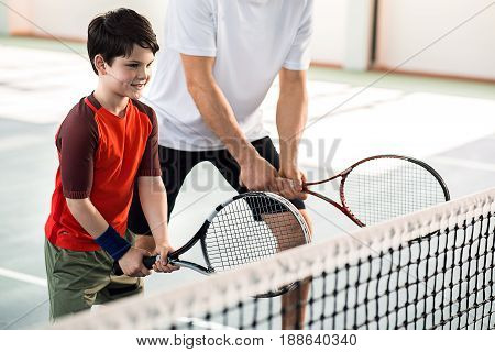 Happy boy is enjoying playtime with his father. He is standing in preparation position and holding racket. Child is smiling. Portrait