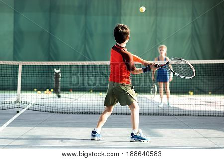 Boy is playing tennis with girl. They are separated by the net on tennis court. Child is turning back to camera