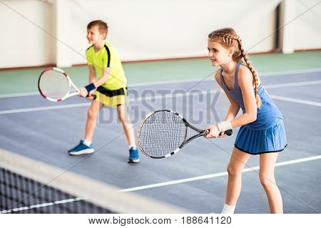 Joyful girl is ready for pitch. She is holding tennis racket and smiling. Boys is standing on background