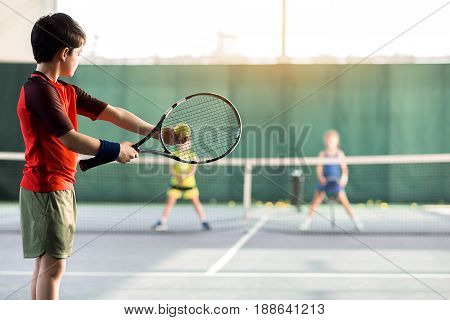 Concentrated boy is pitching tennis ball to children while raising racket. Copy space in right side