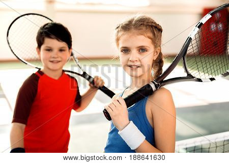 Enjoying playtime. Joyful children are resting after tennis game. They are standing and carrying rackets. Focus on smiling girl