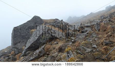 Foggy Mountain panorama Landscape in Himalaya. Rocks and wet grass. Nepal, Annapurna region, Mardi Himal track.