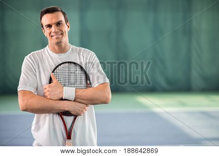 My favorite hobby is tennis. Portrait of happy young man standing on tennis court and hugging racket with joy. He is giving thumb up and smiling. Copy space in right side