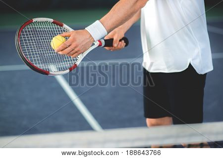 Close up of arms of professional tennis player pitching a tennis ball