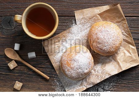 Doughnuts with powdered sugar and cup of tea on a dark wooden background top view