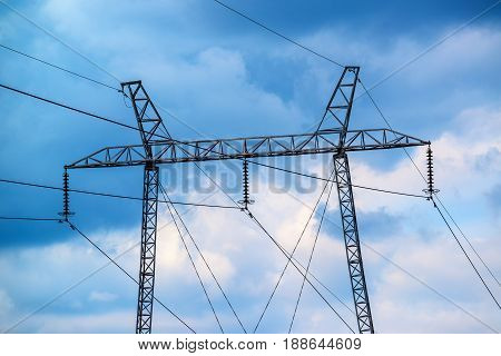 Overhead electricity power line pylon against moody sky