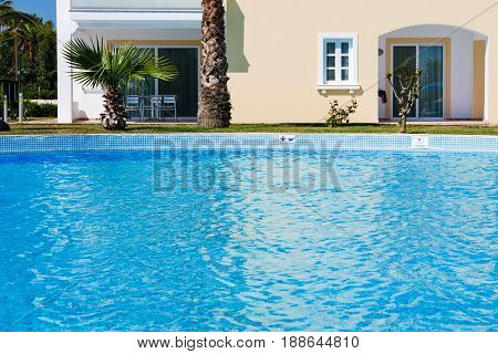 Hotel outdoor swimming pool with clear water and facade of hotels room.