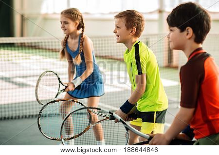 Joyful kids are ready to kick the ball by tennis racquets. They are posing and laughing