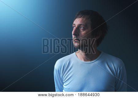 Hopeless man looking up to the light sad and disappointed adult male person in hope concept