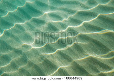 Background of shallow sea water with rippled sand bottom with refraction of reflections light.