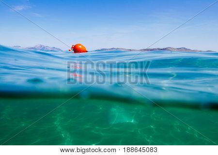 Marker buoy on surface of water. View half and half underwater.
