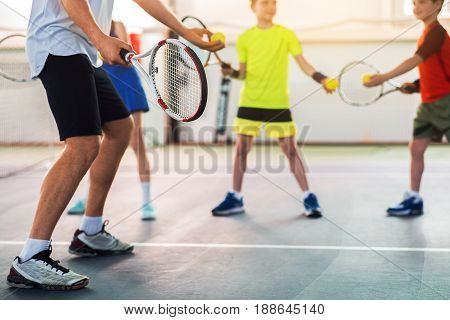 Close up low angle of legs of male tennis coach showing how to pitch the ball. Children are practicing pitch with interest