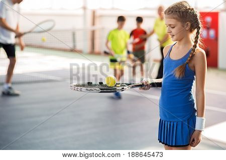 Joyful girl is holding ball on tennis racket with interest. She is standing on tennis court and smiling. Kids and trainers are on background
