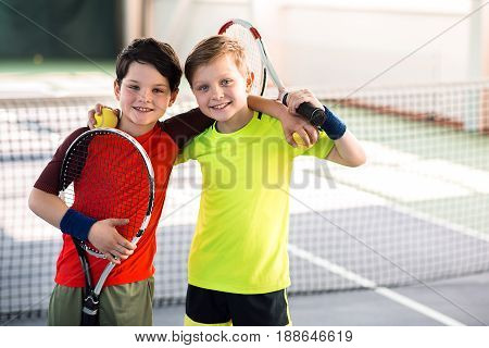 Best friend. Portrait of joyful two boys playing tennis together. They are embracing and smiling. Kinds are holding rackets and balls