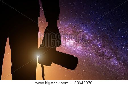 Silhouette photographer with camera and milky way blackground.