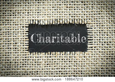 Text Charitable on paper black has Cotton yarn background you can apply to your product.