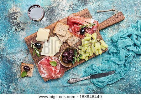 Typical italian antipasto, wooden cutting board with prosciutto, ham, cheese and olives on blue stone background. Top view with copy space