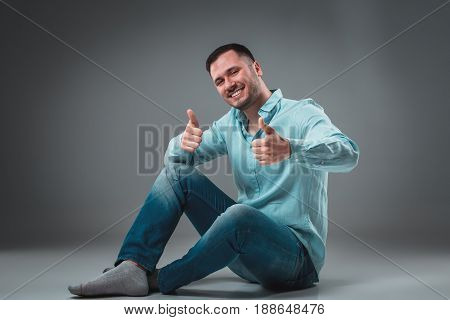 Handsome young man sitting on a floor with raised hands gesturing happiness on gray background. A man in jeans and a blue shirt