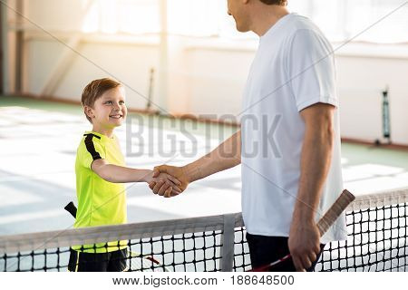 Good game. Trainer and boy are shaking hands while standing near net. They are holding tennis rackets and smiling