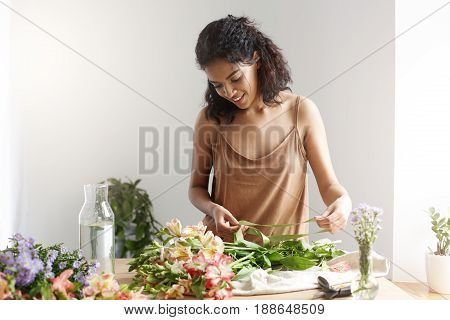 Cheeful african girl florist smiling holding ribbon working with flowers over white wall. Copy space.