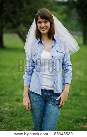 Portrait Of Brunette Girl On Checkered Shirt, Jeans And Veil At Hen Party.