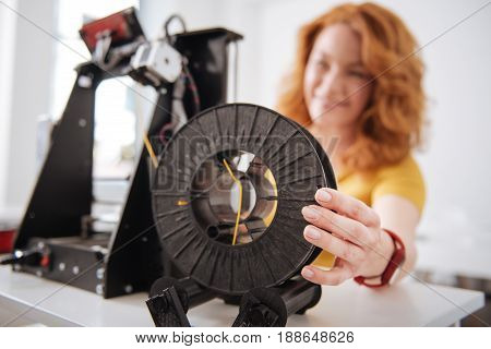 3d printer details. Selective focus of a 3d printer filament being held by a nice pleasant female designer while working with 3d technology