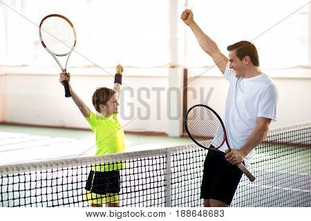 We are winners. Excited father and son are celebrating their triumph in tennis game. They are raising hands in fists and laughing. Man and boy are holding rackets