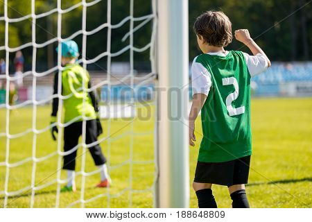 Young boy plays soccer football match on the pitch. Soccer football match for kids. Youth soccer background