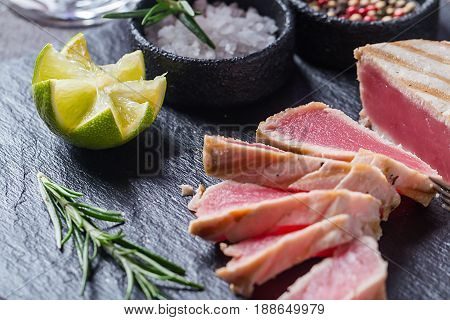 Close up of seared grilled tuna steaks on slate surface with spices and lemon