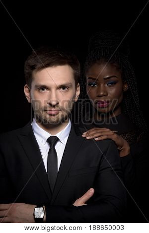 Close up portrait of multi-ethnic couple on black background. Multi-ethnic man and woman posing on black backstage. Man in business suit with dark skinned woman behind.