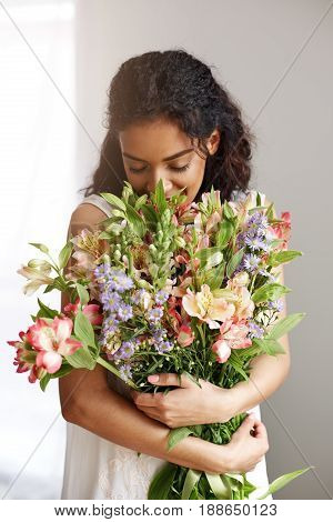 Beautiful african girl florist smiling holding sniffing bouquet of alstroemerias over white wall. Closed eyes.