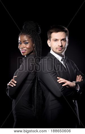 Multi ethnic man and woman standing back to back. Man and woman in black suits on dark background. Dark skinned female together with european man.