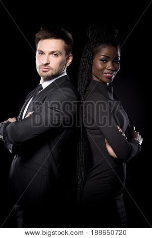 Close up portrait of multi ethnic coupe on black background standing back to back. Multi ethnic man and woman posing together.