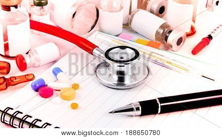 Stethoscope Medical Ampules Pills And Syring On Doctor Notebook For Experiment In Doctor Laboratory.