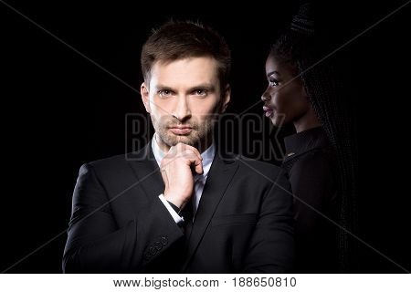 Man in suit standing with hand touching his chin with dark skinned woman behind. European man posing with dark skinned female behind on black background.