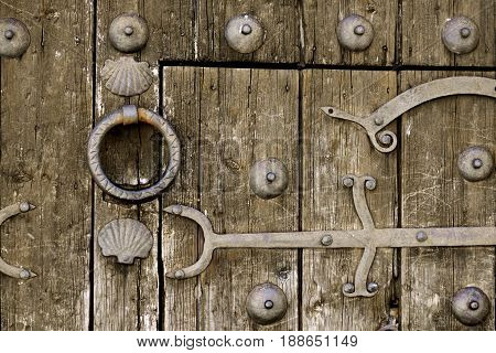 Ancient Wooden Door with Forged Metal Elements and Hinge closeup Outdoors