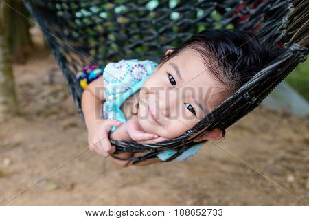 Cheerful child enjoying and relaxing in hammock outdoor at the daytime. Pretty asian girl smiling and looking at camera. Summer vacation or happy time concept.