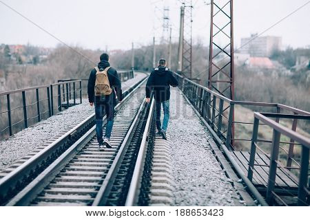 Back view of two men walking away on the railroad tracks