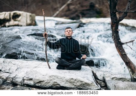Man meditating in Lotus Pose with cliff on waterfall like sensei