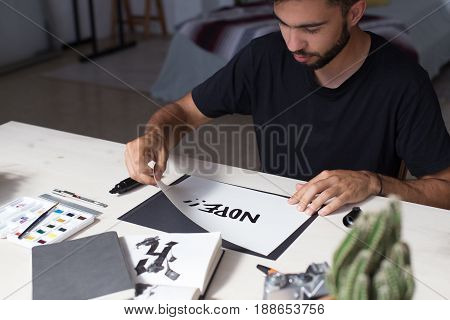 Graffiti calligraphy artist in his home studio in art district finished project concept of student or young enterpreneur in denial refusing to agree with situation text says nope
