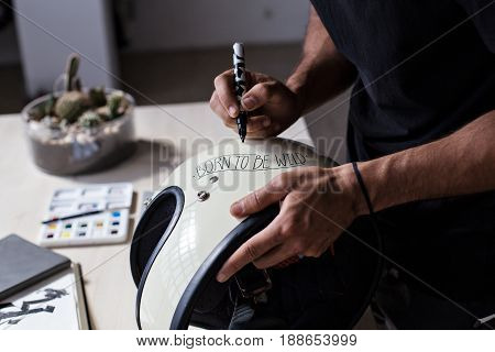 Side shot of manly muscled hands and arms of brutal motorcycle mechanic personalizing moto full face helmet with hand written lettering calligraphy text says born to be free