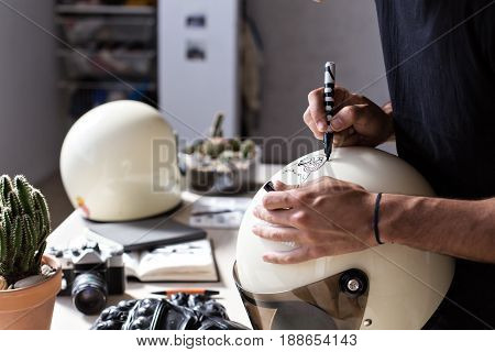 Shot of male muscular hands with ink under finger nails of true artisan craftsman drawing images and illustrations on top of vintage fullface race helmets