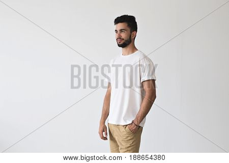 Attractive bearded masculine male poses with hand in his pocket on isolated mockup wall in chinos pants and simple yet stunning white t-shirt made from organic cotton
